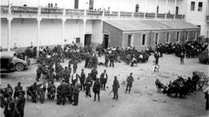 Tropas de Alicante y Murcia armadas vigilan los prisioneros rebeldes desarmados que permacenen sentados en pequeños grupos en el patio del cuartel de Albacete